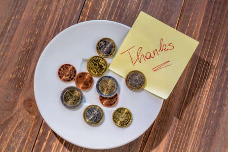 tax tips: a plate of coins for tips or fee for toilets. in english Stock Photo