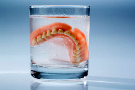 nursing class: a denture is cleaned in a glass of water. proper hygiene. Stock Photo