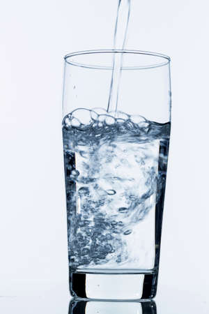 purely: water is poured into a glass, symbolic photo for drinking water, freshness, supplies and consumables