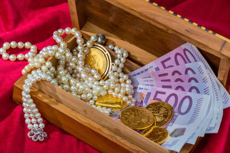 assessment system: gold coins and bars with decorations on red velvet. photo icon for wealth, luxury, wealth tax.
