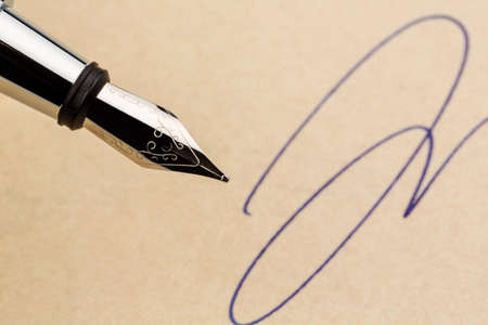 notieren: a signature and a fountain pen on yellow paper. symbolic photo for contract, testament and graphology