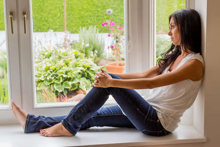 psychologically: a young woman sitting by the window and relax
