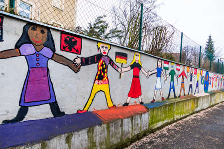 on the wall of a school children have students painted. symbolic photo for coexistence and migration