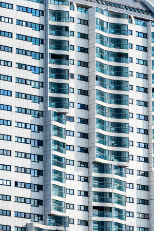 many windows: a high-rise building in vienna for homes and offices. facade with many windows Stock Photo