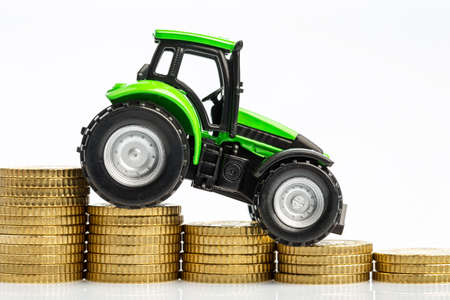 peasantry: farmers in agriculture have to reckon with rising costs. higher preies in feed, fertilizer and plants. tractor with coins Stock Photo