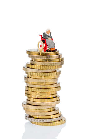 care allowance: woman in wheelchair on money stack symbol photo for care allowance, health care costs