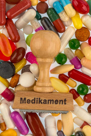 therapie: stamp on colorful tablets, symbolic photo for drug therapy and prescription