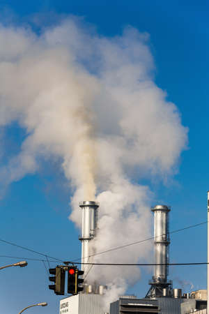 ozone: chimney of an industrial company and red traffic lights. symbolic photo for environmental protection and ozone. Stock Photo