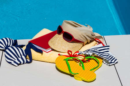 utensils for a nice relaxing vacation day lying next to a swimming pool. relaxation on vacation. photo