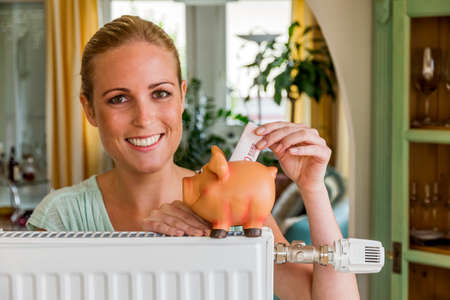 natural gas prices: a young woman with a radiator and a piggy bank. photo icon for saving energy and heating