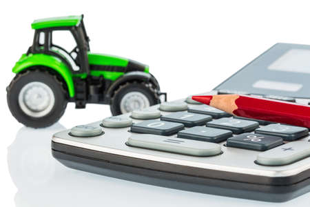 subsidy: a tractor and a red pen lying on a calculator. cost of gasoline, wear and insurance. costs and subsidies in agriculture