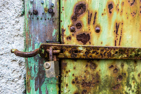 durability: rusted lock a door, a symbol of decay, damage, transience Stock Photo
