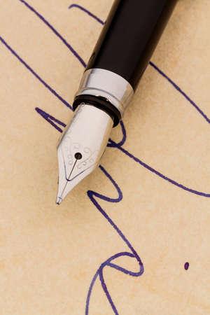 testament schreiben: eine Signatur und einem Füllfederhalter auf gelbem Papier. Symbolfoto für Vertrag, Zeugnis und Graphologie Lizenzfreie Bilder