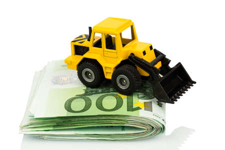 subsidy: an excavator stands on euro banknotes. symbolic photo for cost, revenue and grants in the construction industry and the construction industry