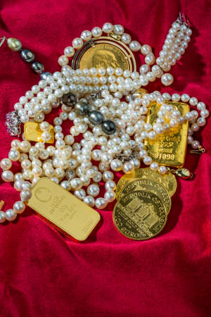 monetary devaluation: gold coins and bars with decorations on red velvet. photo icon for wealth, luxury, wealth tax.