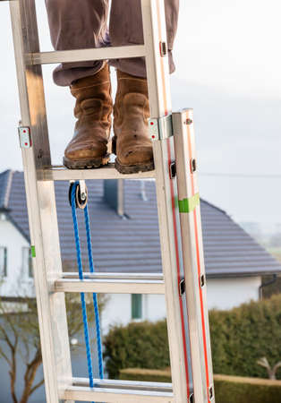 safety boots: craftsman on a ladder at the house, icon crafts, home improvement, safety, career Stock Photo