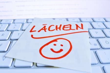 trato amable: una nota en el teclado de una computadora como una sonrisa recordatorio
