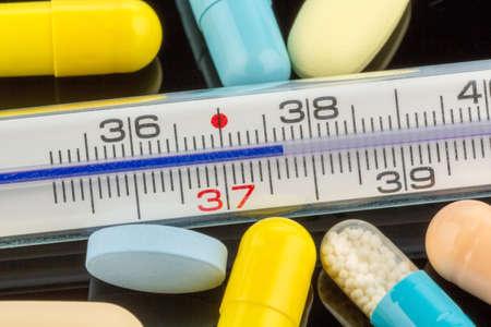 gripe: un termómetro y tabletas clínica. Foto simbólica para la gripe y los resfriados Foto de archivo