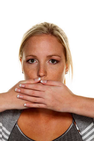 deny: a young woman holds her hand to her mouth. symbolic photo for silent, say nothing and deny the statement Stock Photo