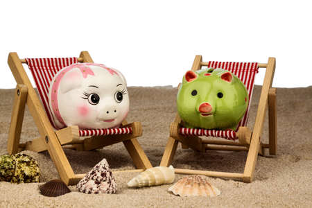 and is favorable: beach chair with piggy bank on the sandy beach. symbolic photo for cost of travel, vacation, holidays. save on vacation