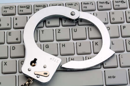 misuse: handcuffs lying on the keyboard of a computer. symbolic photo for crime, computer crime and misuse of data. Stock Photo