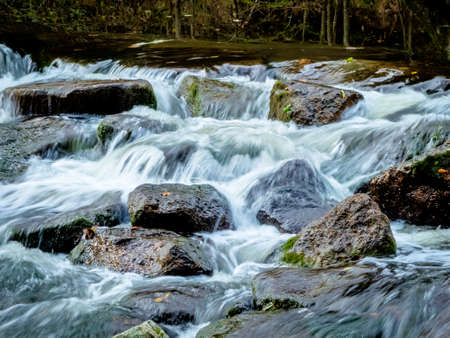 fluent: a creek with rocks and flowing water. landscape experience in nature. Stock Photo