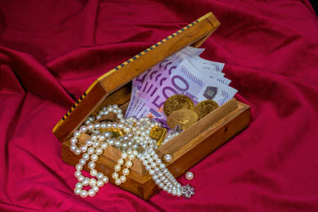 namacalny: gold coins and bars with decorations on red velvet. photo icon for wealth, luxury, wealth tax.