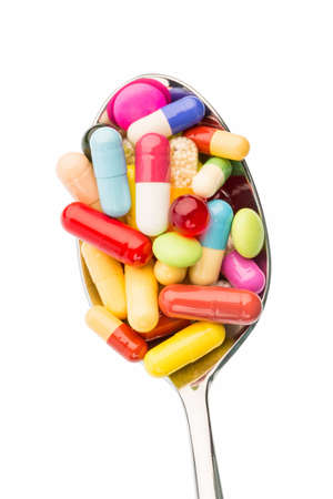 investigated: many colorful pills on a spoon. photo icon for tablets addiction and abuse of drugs.