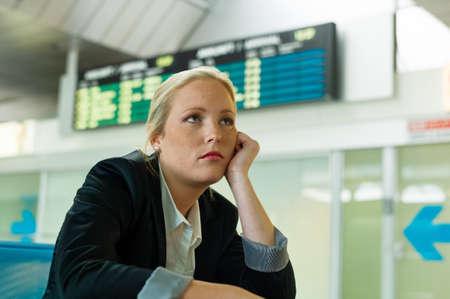 persona viajando: empresaria esperando su salida en el aeropuerto. foto simbólica de los retrasos, cancelaciones de vuelo y huelgas. Foto de archivo