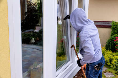 criminals: a burglar trying to break in an open window with a crowbar