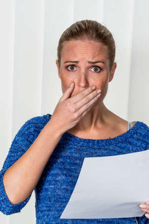 dimissal: a young woman gets bad news in a letter in the mail
