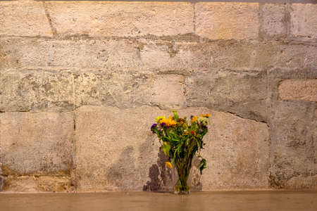 flowers in front of a stone wall, a symbol of decoration, transience,