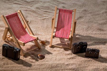 kkleine deck chairs on sandy beach with suitcase photo