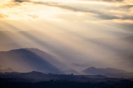 breaking through: sun rays breaking through the clouds over a mountain landscape