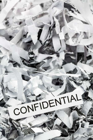 paper shredder: shredded paper tagged with confidential, symbolic photo for data destruction, banking secrecy and confidentiality