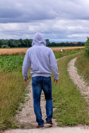 unrelated: a man walks alone on a path. Stock Photo
