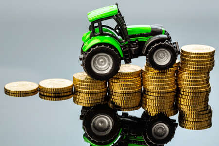 reckon: farmers in agriculture have to reckon with rising costs. higher prices for food, fertilizer and plants. tractor with coins