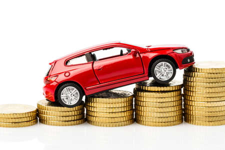 pkw: car on coins. symbol photo for costs Stock Photo