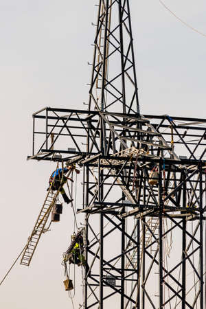 energy needs: construction of a new high-voltage line. workers on electricity pylons