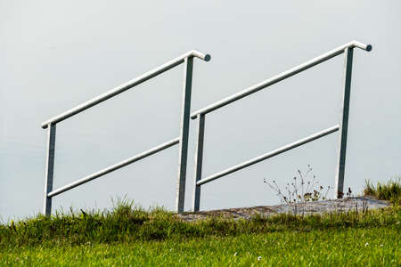 downstream: railing on the shore, a symbol of security. also for downstream and resort Stock Photo