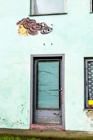 subcultures: woman faces on a house wall, a symbol of creativity, beauty and art. former firsörladen