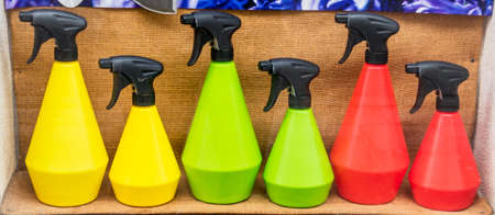 spray bottle: colorful spray bottles in the window, symbol of flowers maintenance, assortment, plastic products, traffic lights