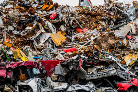 scrap trade: old cars were scrapped in a trash compactor. scrap iron and scrapping premium for car wrecks