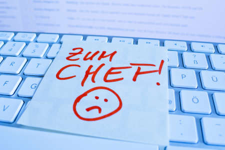 a memo is on the keyboard of a computer as a reminder: for chef Stock Photo