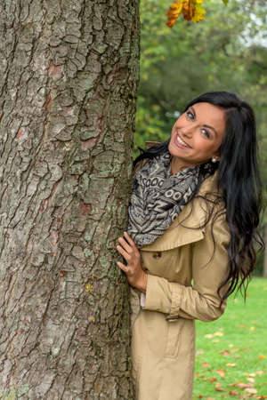 a young woman looks out from behind a tree Stock Photo