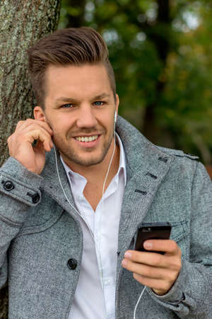 hark: a man listens to music with your phone. talking on mobile phone.