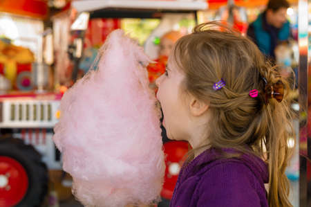 joie: a little girl on a kirtag with cotton candy. fun and enjoying fairground