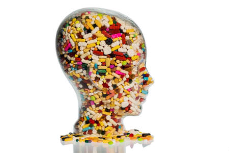 abuse: a head made of glass filled with many tablets. photo icon for drugs abuse and painkillers.