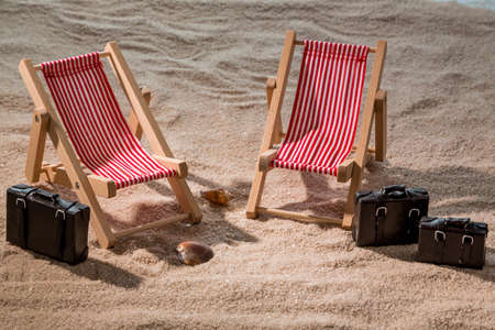 deck chairs: kkleine deck chairs on the sandy beach with suitcases Stock Photo