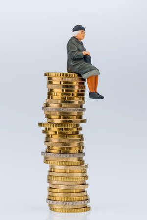 oldage: pensioner sitting on money stack, symbol photo for retirement, pension, old-age insurance